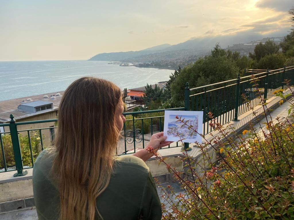 Yvonne vergleicht ihre Postkarte aus Monte Carlo mit dem Blick auf das Meer