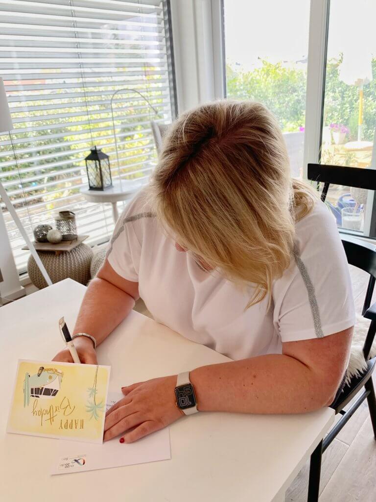 Ulrike schreibt zum Weltpostkartentag eine Glückwunschkarte.
